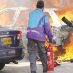 KESC Karachi Workers Wrath - Officials extinguish a burning car torched by sacked employees inside parking lot during protest on Janaury 20, 2011