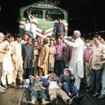 Pay Employees Salaries - Railway workers lie in front of the engine shed exit