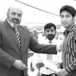 Chairman POF Ahsan Mahmood giving scholarship to a student